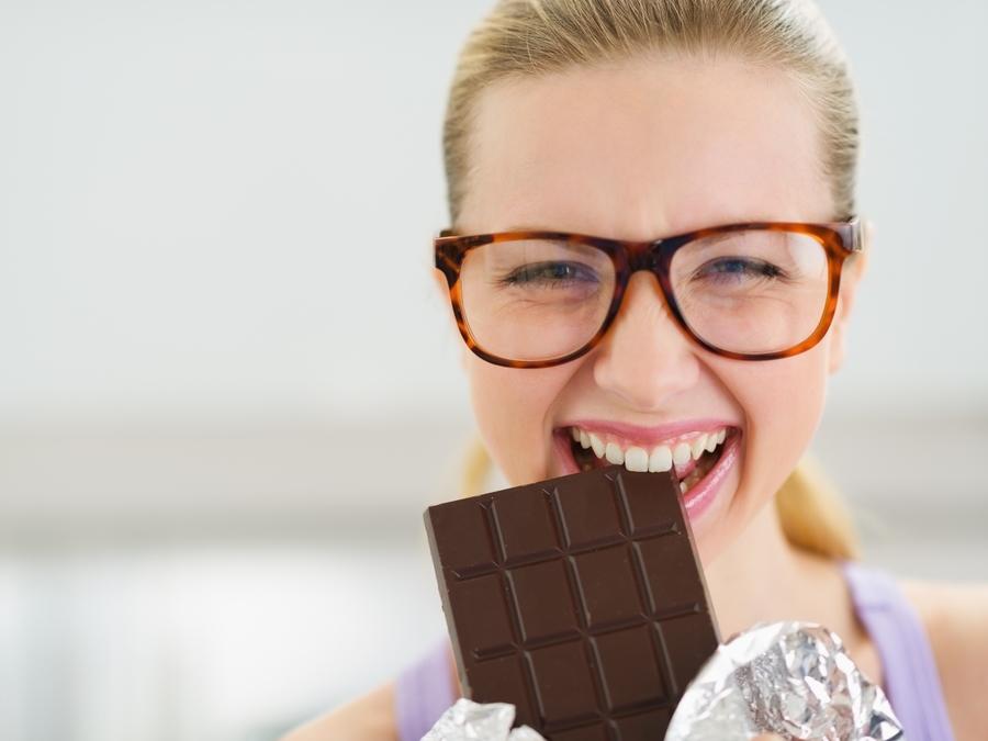 Happy girl eating chocolate